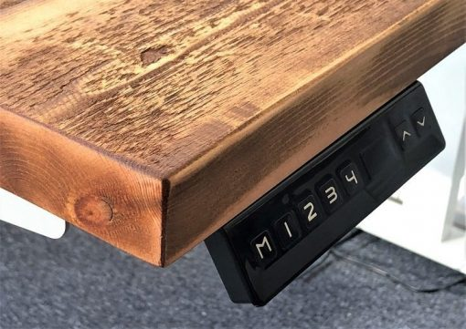 Adjuster buttons on rustic pine height adjustable electric standup desk.